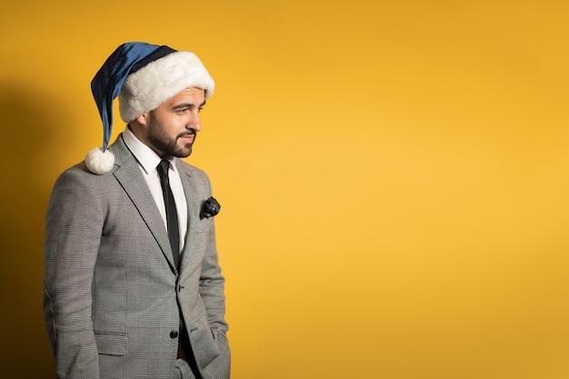 Стильный вдумчивый красавец в синей шляпе и костюме санта-клауса, смотрящий вперед, изолированный на желтой стене