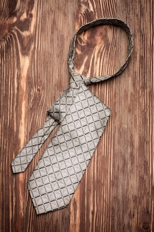 Stylish tie for man on wooden table.