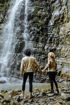 Stylish tourist couple, man and woman, dressed in beautiful chickens, stand holding hands in front of a large waterfall