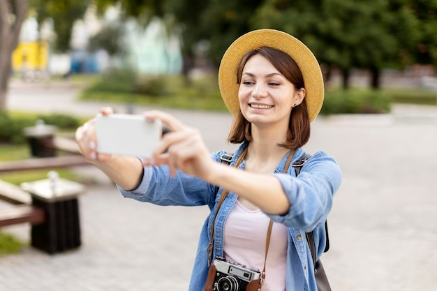 Stylish tourist with hat taking pictures
