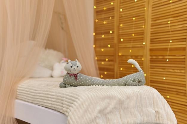 かわいい子供部屋のインテリアのベッドの上の長い猫のスタイリッシュなおもちゃ