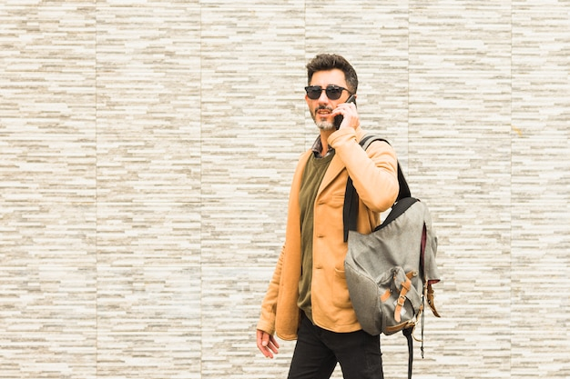 Stylish traveler standing against wall talking on mobile phone
