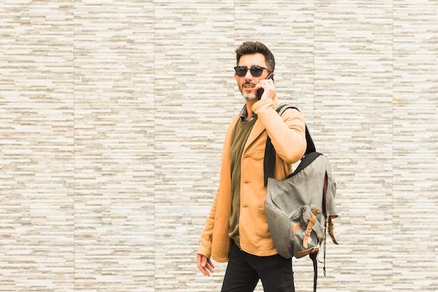 Стильный путешественник, стоящий у стены, разговаривает по мобильному телефону