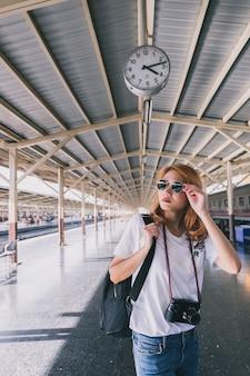 Stylish traveler with backpack on station