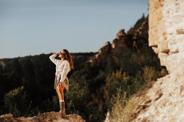 山でリラックスするスタイリッシュな旅行者の女性