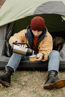 Stylish traveller pouring drink in cup