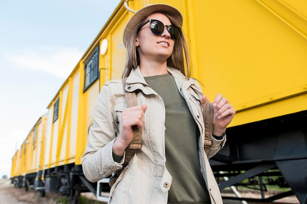 帽子とサングラスを持つスタイリッシュな旅行者