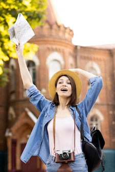 Viaggiatore alla moda con cappello che tiene la mappa locale
