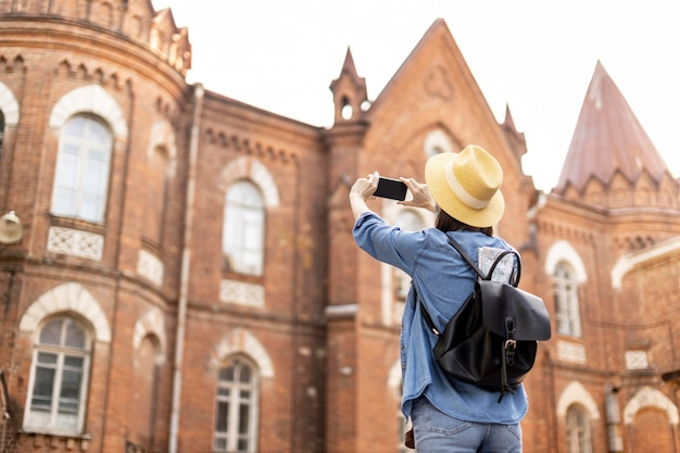 Stylish traveller with hat taking pictures on holiday
