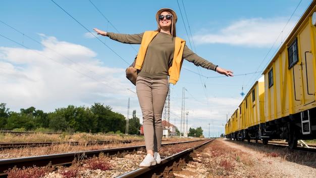 鉄道の上を歩く帽子を持つスタイリッシュな旅行者