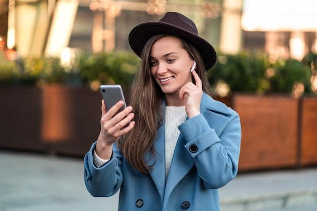 帽子と青いコートを着たスタイリッシュなトレンディなブルネットヒップスターの女性。市内中心部でスマートフォンとワイヤレスホワイトヘッドフォンを使用してオンラインで友達とチャット。現代人とテクノロジー