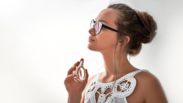 白いブラウスと白い壁にお気に入りの香水を適用するガラスのスタイリッシュなトレンディなブルネットの女性。コピースペース