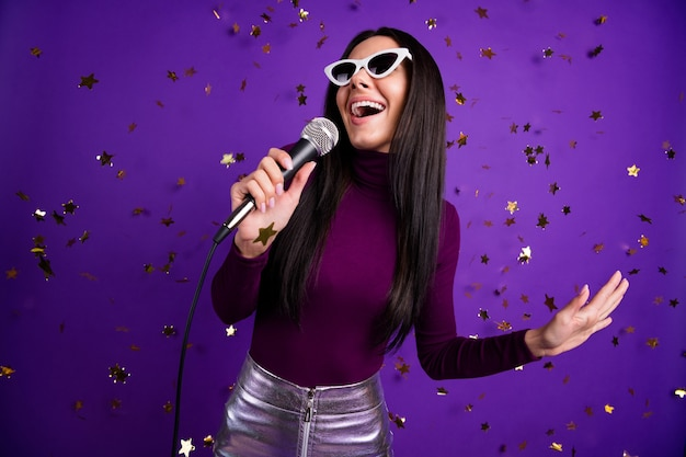 Stylish trendy casual girlfriend singing into microphone enjoying her being at karaoke bar isolated bright color wall purple
