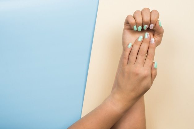 Stylish trendy female blue new manicure with hearts and the words love on the nails. beautiful young woman's hands