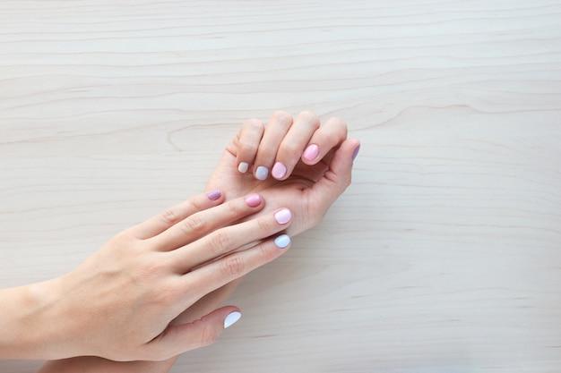 세련된 유행 여성 파스텔 흰색, 분홍색 및 파란색 매니큐어. 나무 바탕에 아름 다운 젊은 여자의 손입니다. 공간 배너를 복사합니다.