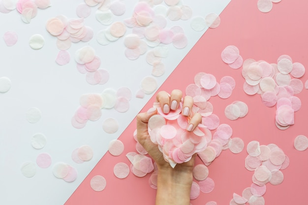 Stylish trendy female pink manicure and confetti