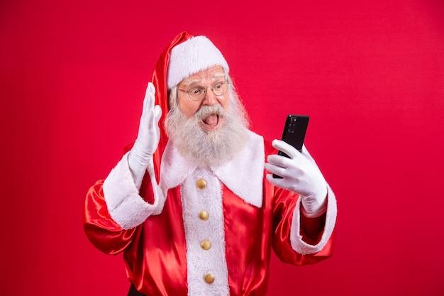 Стильный модный дедушка в возрасте зрелых традиций санта-клауса, зимний костюм, головные уборы, очки с белой бородой, принимает рождественскую селфи-картинку переднюю камеру на красном фоне.