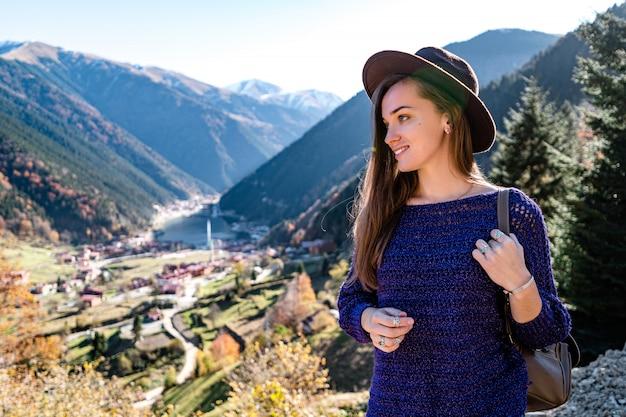 トルコ旅行中に山のバックパックとトラブゾンのウズンゴル湖と茶色の帽子でスタイリッシュなトレンディな幸せな流行に敏感な女性旅行者