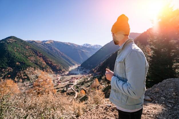 トルコの旅行中に山とトラブゾンのウズンゴル湖に立つ黄色の帽子とデニムジャケットのスタイリッシュな流行の流行に敏感な男性旅行者