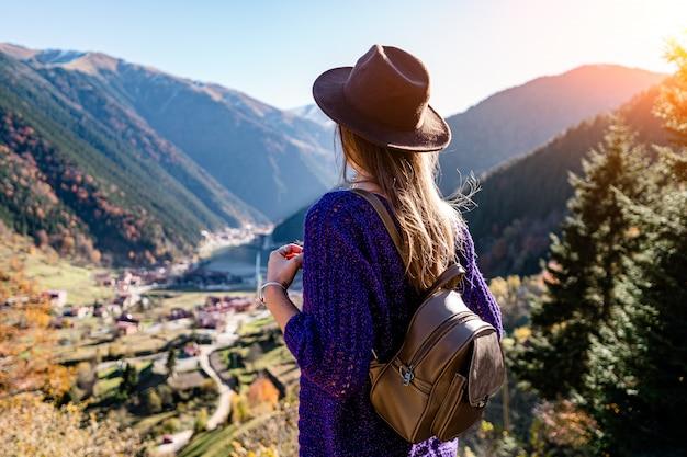 トルコ旅行中に山とトラブゾンのウズンゴル湖の上に立つ茶色のバックパックとフェルト帽子のスタイリッシュな流行の流行に敏感な女性旅行者