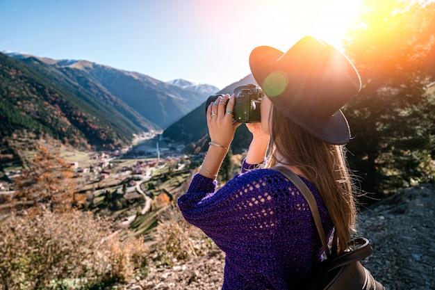 トルコ旅行中に山とトラブゾンのウズンゴル湖の写真を撮る茶色のバックパックとフェルト帽子のスタイリッシュな流行の流行に敏感な女性旅行者カメラマン