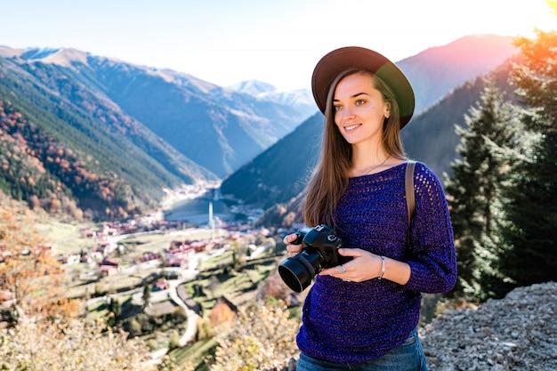 トルコ旅行中にトラブゾンの山とウズンゴル湖の写真を撮っている間にフェルト帽子のカメラでスタイリッシュな流行の流行に敏感な女性旅行者写真家