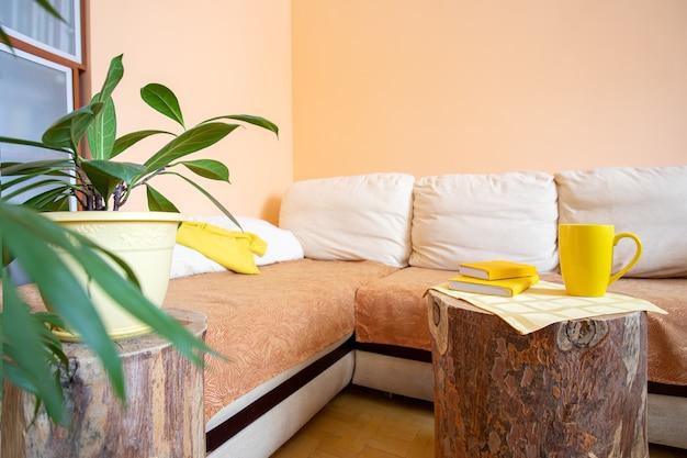 대형 코너 소파, 그린 하우스 식물 및 창의적인 테이블 또는 꽃 스탠드와 같은 둥근 나무 그루터기로 세련되고 트렌디 한 조명 홈 실제 인테리어.