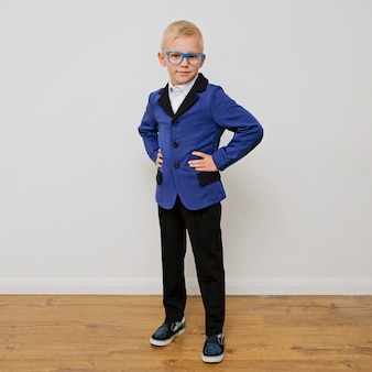 Stylish trendy little boy in glasses wearing a suit.