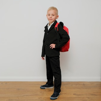 Stylish trendy little boy in a suit with a school bag.