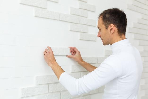 Стильная модная белая керамическая плитка с фаской на стене кухни. плиточник руки в процессе укладки белой прямоугольной плитки на стене ванной комнаты. ремонт квартир и ванных комнат.