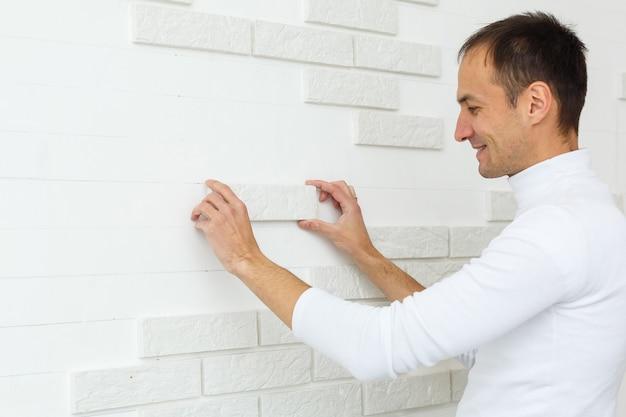 キッチンの壁に面取りが施されたスタイリッシュなトレンディな白いセラミックタイル。タイル張りの手は、白い長方形のタイルを浴室の壁に敷く過程にあります。アパートやバスルームの修理。