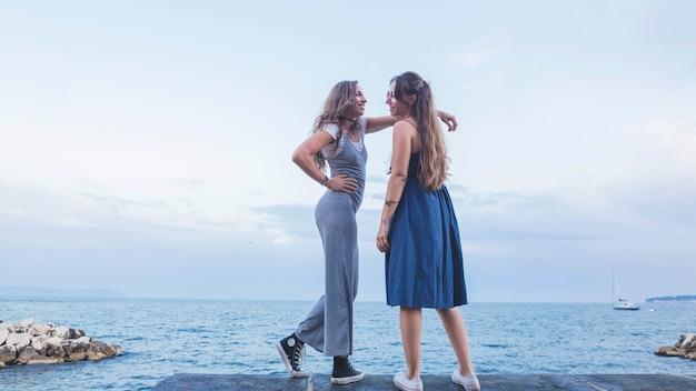 푸른 바다와 하늘에 서있는 세련된 두 젊은 여자 친구
