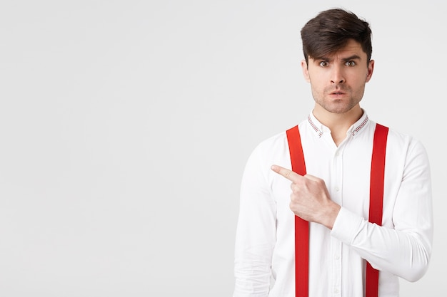 Stylish unshaved dark-haired guy resents with indignant facial expression, pointing with index finger to the left side