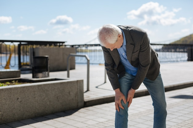 Stylish upset confusing pensioner expressing discomfort and afflicting with knee while going home