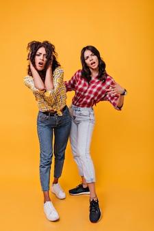 Eleganti ragazze urbane emotivamente pongono. adolescenti in jeans e scarpe da ginnastica dall'aspetto patetico.