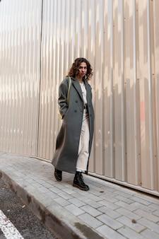 가방과 부츠가 달린 세련된 긴 녹색 코트에 곱슬머리를 한 세련된 도시 힙스터 소녀가 금속 벽 근처 거리를 걷습니다.