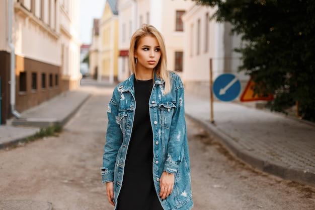 빈티지 건물 근처 거리에 도시에서 포즈 유행 긴 데님 재킷에 검은 세련된 드레스에 세련된 도시 예쁜 젊은 여자
