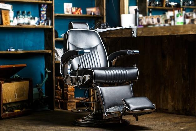 Стильное винтажное кресло для парикмахера. тема парикмахерской. профессиональный парикмахер в интерьере парикмахерской.