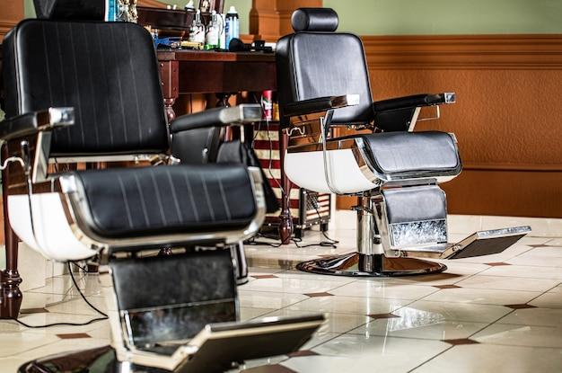 Стильное винтажное кресло для парикмахера. профессиональный парикмахер в интерьере парикмахерской. стул парикмахерской
