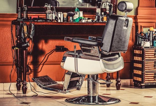 スタイリッシュなヴィンテージの理髪店の椅子。理髪店のインテリアのプロのヘアスタイリスト。