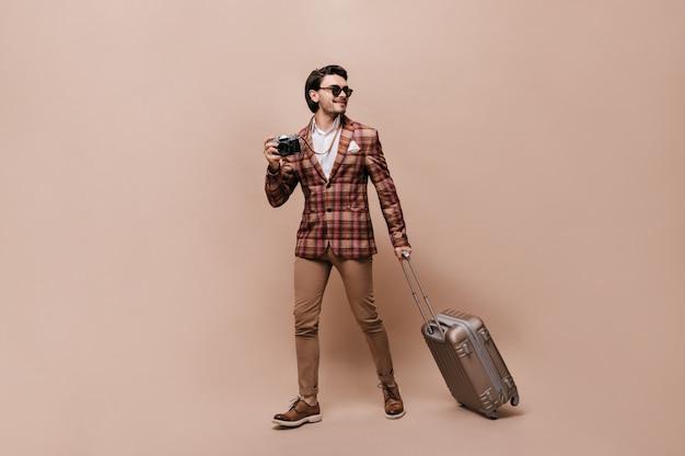 Стильный путешественник в бежевых брюках, коричневых кожаных туфлях, клетчатой куртке, держит фотоаппарат и чемодан, в солнечных очках, позирует у персиковой стены и смотрит в сторону.