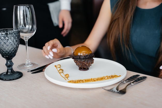 A stylish waiter in an apron serves a young girl in a fine restaurant and serves her a unique dessert covered with food gold. customer service.