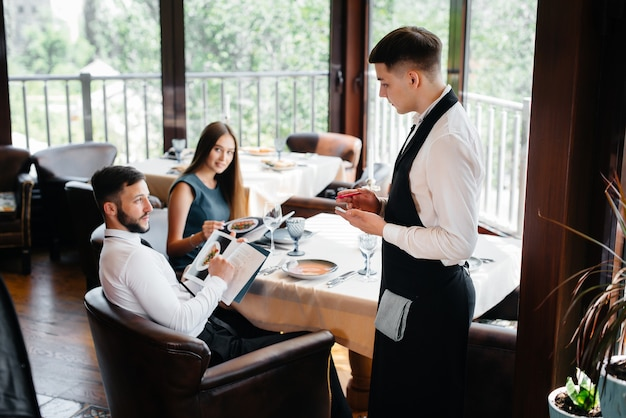 A stylish waiter serves a young couple who came on a date in a gourmet restaurant. customer service in the catering.
