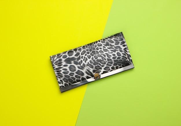Стильный кошелек на зеленой пастели. модный минимализм.
