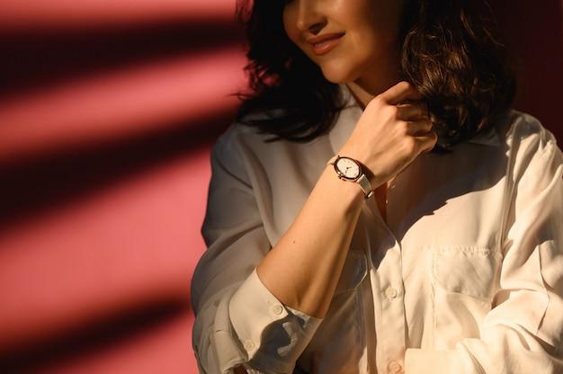 女性の手にスタイリッシュな時計。ゴールデンアナログ腕時計