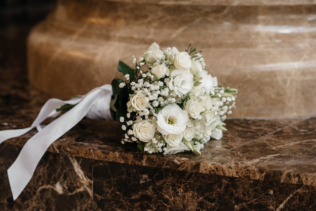 Stylish wedding bouquet close-up on the marble floor.