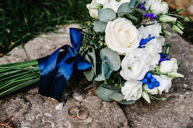 Stylish wedding bouquet flowers from bush roses, eustoma and gold wedding rings on the stone. wedding ceremony. close up.