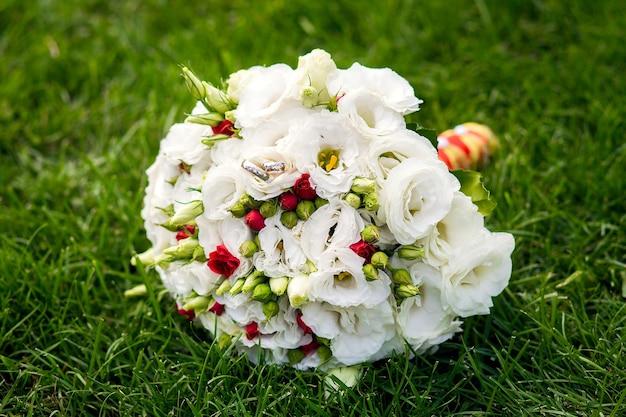 Стильный свадебный букет из живых цветов на зеленой лужайке. детали свадебного декора.