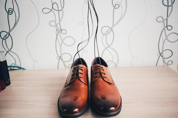 Стильные свадебные коричневые мужские туфли, лежащие на светлом столе. аксессуары жениха. шнуровка поднята вверх и сливается с полосатыми обоями.