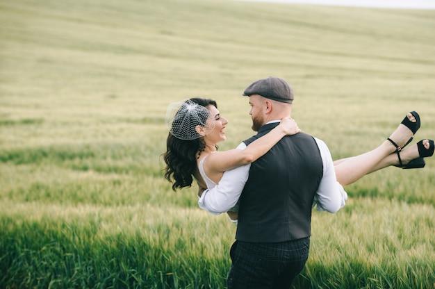 Стильная свадьба пара в зеленом поле возле ретро автомобилей.